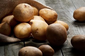 Kartoffeln im Sack auf Holzbrett