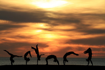 Wall Mural - group of gymnasts tumbling in sunset