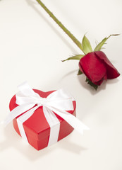 Heart-shaped Valentines Day gift box with rose over a white