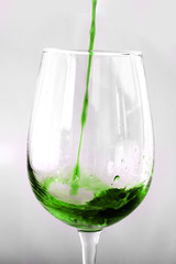 Green wine being pured in to a wine glass