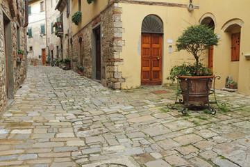 narrow italian street and small patio in tuscan village