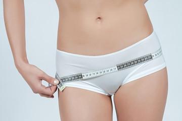 femme mesurant sa taille fine plat en boxer blanc