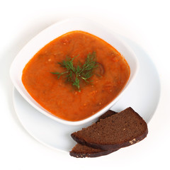 Image of bowl of hot red soup and bread isolated