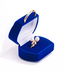 gold ring with pearls in blue velvet gift box on white
