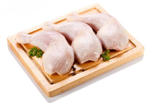 Raw chicken legs on cutting board on white background
