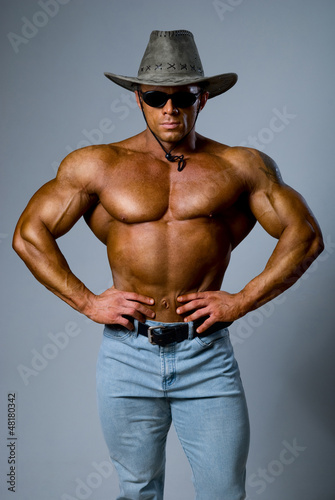 Handsome muscular man wearing a hat and sunglasses