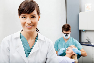 Female Assistant With Dentist Working In The Background