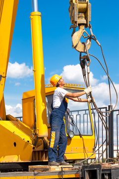Construction worker during hoisting works by a mobile crane