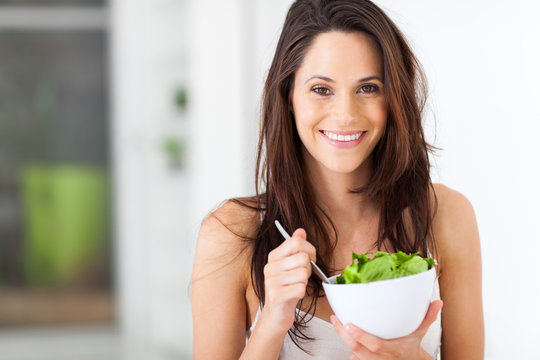 attractive young woman eating healthy salad
