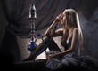 A young blond woman in erotic lingerie smoking a hookah