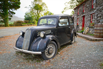 Vintage car on the front of Irish cottage house