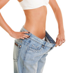 woman shows her weight loss by wearing an old jeans, isolated o