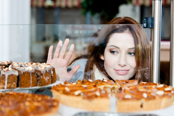Lady  looking at the bakery window full of cakes
