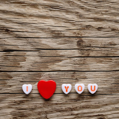 I love you text on miniature hearts on wooden background