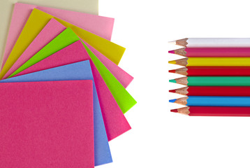Colorful pencils and note papers on white