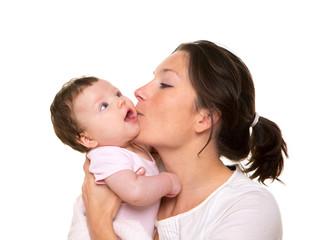 Beautiful mother kissing baby girl hug on white