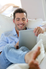 Cheerful young man laying in sofa with digital tablet