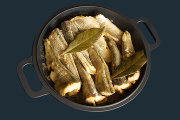 Appetizing fried fish on pan isolated on blue closeup