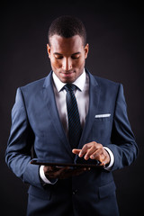 Young business man with a digital tablet on black background