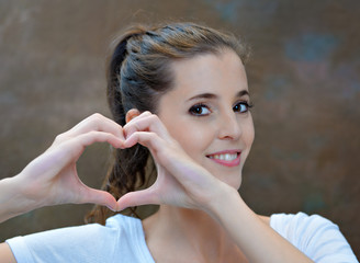 Portrait of a young woman making a heart shape sign with her han