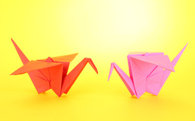 Origami cranes on yellow background.