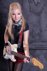 teenager rockstar with electric guitar against wall background
