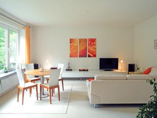 modernes Wohnzimmer und Esszimmer weiß mit hellem Teppichboden und weißem Sofa