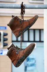 Two old shoes hanging on a pole