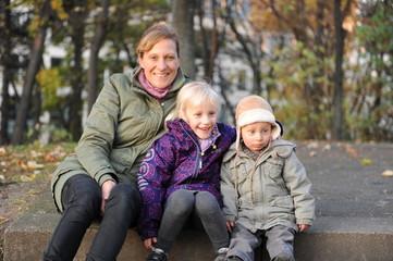 Mutter mit zwei Kindern auf dem Spielplatz