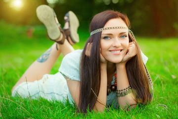Smiling hippie girl on green grass