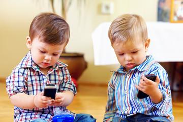 cute baby toddlers exploring mobile phones