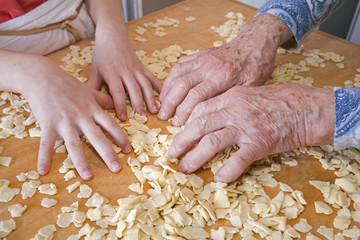 hands of grandmother and grandchild at cooking