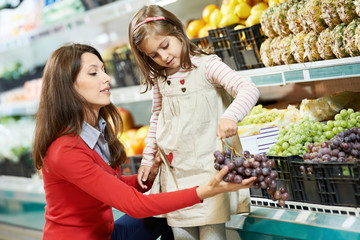 mother and girl shopping in supermarket
