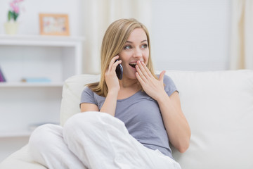 Casual surprised woman using cellphone at home