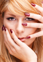 Beautiful blond girl holding her hands in front of her face