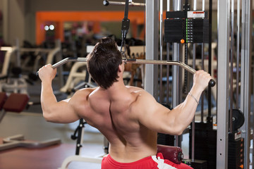 Rear view of young fitness guy working out on exercise machine