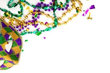 Wall Mural - A Mardi gras mask and beads on a white background with copy spac