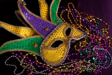 Wall Mural - A Mardi gras jester's mask with beads on a black background