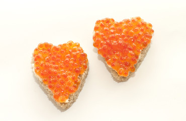 Two sandwich in the form of a heart with red caviar