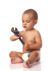 Cute little boy holding an adjustable spanner over white