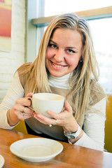 smiling young woman drinking coffee from a white cup