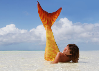 beautiful mermaid lying in the tropical sea
