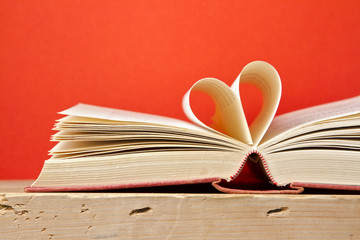 Book with pages folded in heart shape over red background