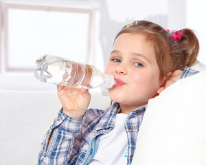 portrait of a cheerful little girl drinking water from a bottle