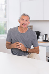 Smiling man holding a cup