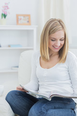 Happy casual woman reading magazine at home