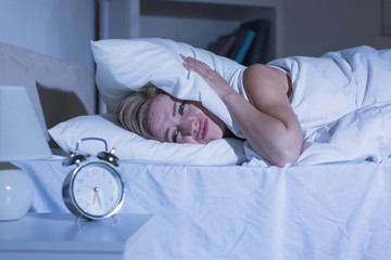 Woman covering ears with pillow as alarm clock rings