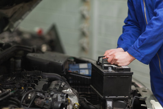 Mechanic changing car battery