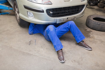 Mechanic working under car