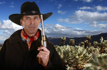 Cowboy with gun touching hat in cholla garden